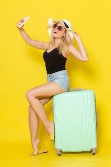 Widok z przodu młoda kobieta na wakacjach siedzi na torbie biorąc selfie na żółtej ścianie kolor dziewczyna kobieta podróż podróż morze