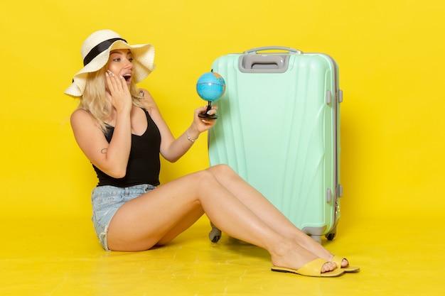 Widok z przodu młoda kobieta na wakacjach siedzi z jej zieloną torbą trzymając kulę ziemską na żółtej ścianie kobieta podróż podróż morski kolor słońca