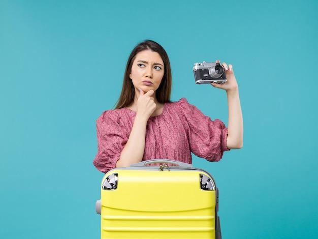 Widok z przodu młoda kobieta na wakacjach trzyma aparat fotograficzny i myśli na niebieskim tle podróż wycieczka morska kobieta za granicą wakacje