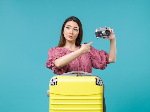 Widok z przodu młoda kobieta na wakacjach trzymając aparat fotograficzny na niebieskim tle podróż wycieczka morska kobieta za granicą wakacje