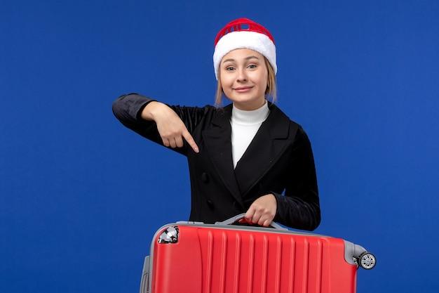 Widok z przodu młoda kobieta niosąca czerwoną torbę na niebieskiej ścianie wycieczka wakacyjna kobieta