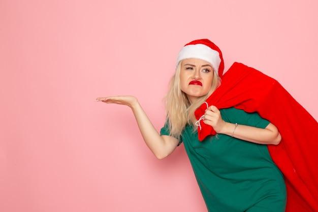 Widok z przodu młoda kobieta niosąca czerwoną torbę z prezentami na różowej ścianie model holiday xmas nowy rok kolor santa