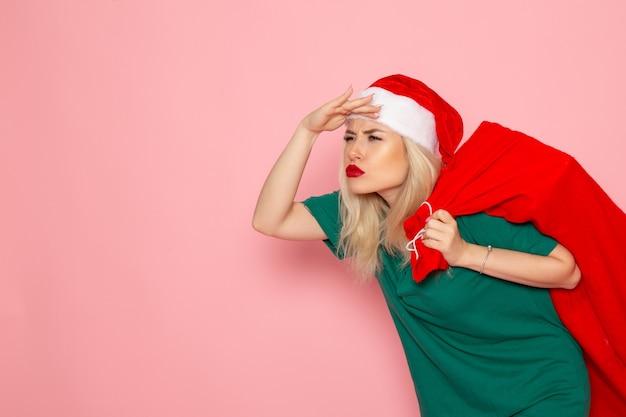 Widok z przodu młoda kobieta niosąca czerwoną torbę z prezentami na różowej ścianie model holiday xmas nowy rok zdjęcie santa