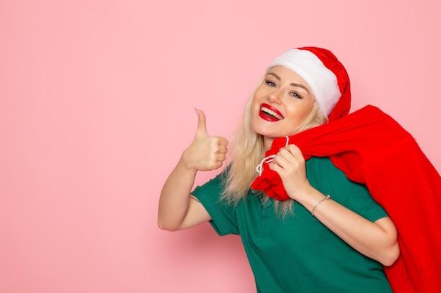 Widok z przodu młoda kobieta niosąca czerwoną torbę z prezentami na różowej ścianie model wakacje boże narodzenie nowy rok zdjęcie kolor santa