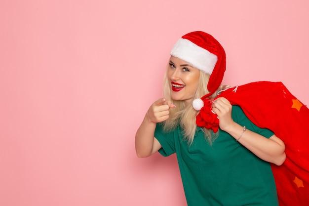 Widok z przodu młoda kobieta niosąca czerwoną torbę z prezentami na różowej ścianie model wakacje boże narodzenie nowy rok zdjęcie kolorystyczne santa