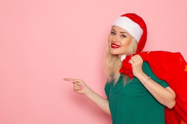 Widok z przodu młoda kobieta niosąca czerwoną torbę z prezentami na różowej ścianie model wakacje boże narodzenie nowy rok zdjęcie santa