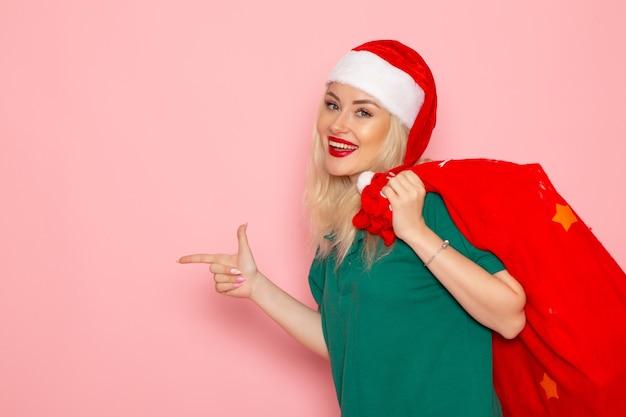 Widok z przodu młoda kobieta niosąca czerwoną torbę z prezentami na różowej ścianie model wakacyjny boże narodzenie nowy rok kolor santa