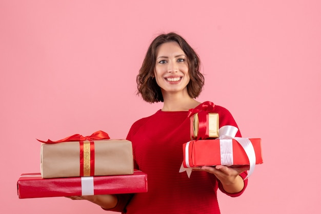 Widok z przodu młoda kobieta niosąca prezenty na różowo