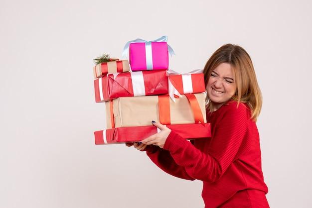 Widok z przodu młoda kobieta niosąca prezenty