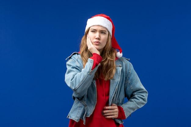 Widok z przodu młoda kobieta o bólu zęba na niebieskim tle boże narodzenie emocje kolor