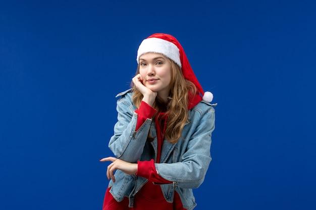 Widok z przodu młoda kobieta po prostu pozuje na niebieskim tle kolor emocji święta bożego narodzenia