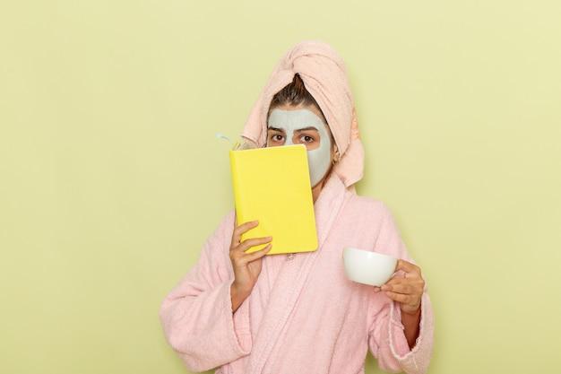 Widok z przodu młoda kobieta po prysznicu w różowym szlafroku, picia kawy i czytania zeszytu na zielonym biurku