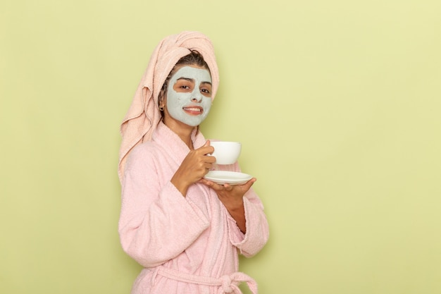 Widok z przodu młoda kobieta po prysznicu w różowym szlafroku picia kawy na zielonej powierzchni