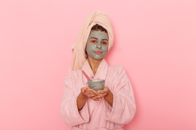 Widok z przodu młoda kobieta po prysznicu w różowym szlafroku stosując maskę na jasnoróżowej powierzchni