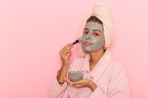 Widok z przodu młoda kobieta po prysznicu w różowym szlafroku stosując maskę na różowej powierzchni