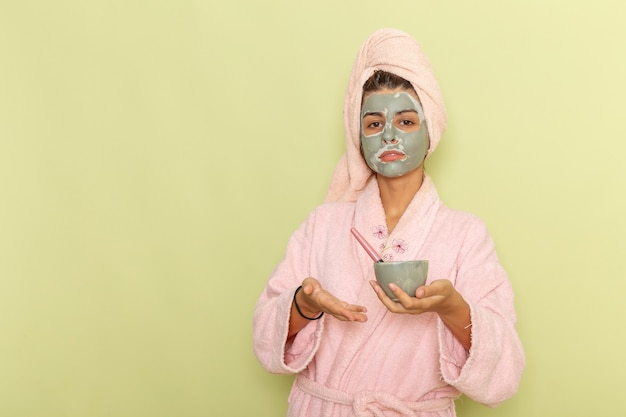Widok z przodu młoda kobieta po prysznicu w różowym szlafroku stosując maskę na zielonej powierzchni