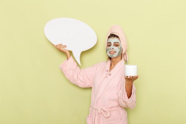 Widok z przodu młoda kobieta po prysznicu w różowym szlafroku, trzymając krem i biały znak na zielonej powierzchni