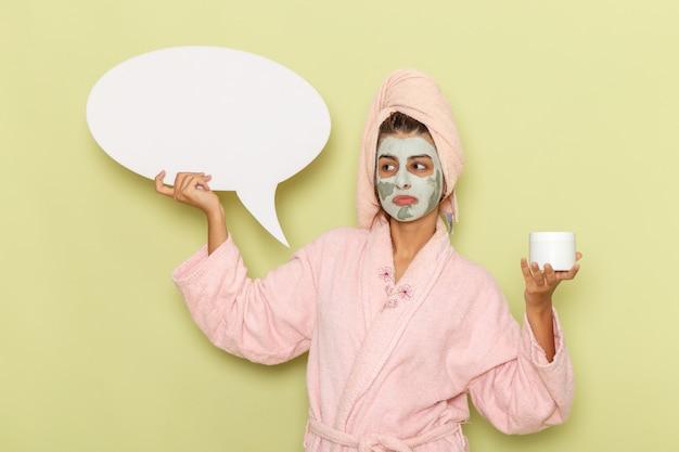 Widok z przodu młoda kobieta po prysznicu w różowym szlafroku, trzymając krem i biały znak na zielonym biurku