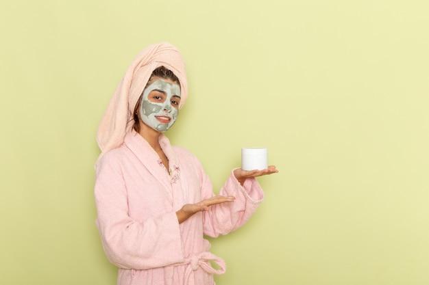 Widok z przodu młoda kobieta po prysznicu w różowym szlafroku trzymając krem na zielonej powierzchni