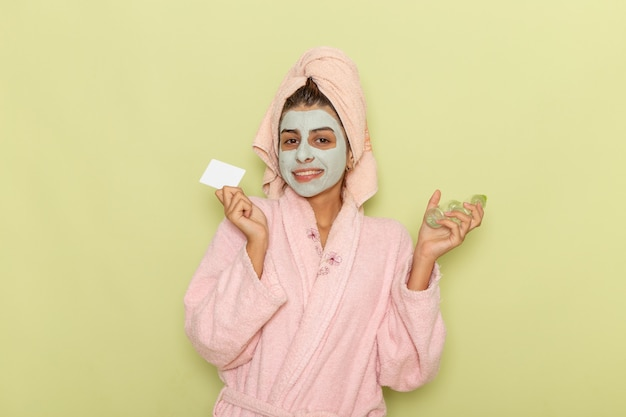 Widok z przodu młoda kobieta po prysznicu w różowym szlafroku trzymając spraye i kartę na zielonym biurku
