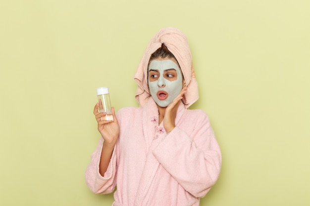 Widok z przodu młoda kobieta po prysznicu w różowym szlafroku trzymając środek do demakijażu na zielonej powierzchni