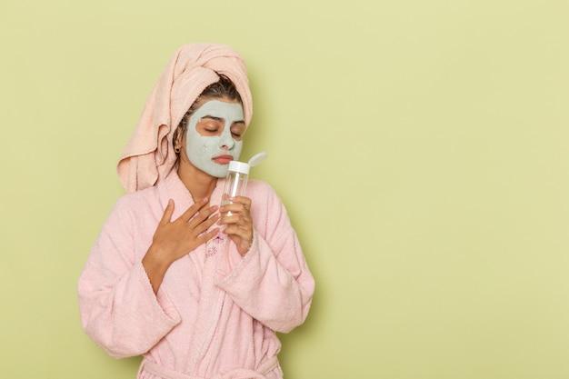 Widok z przodu młoda kobieta po prysznicu w różowym szlafroku trzymając środek do demakijażu na zielonym biurku