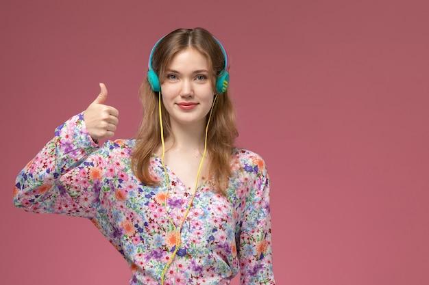 Widok z przodu młoda kobieta pokazuje kciuki do góry i słucha piosenki w słuchawkach