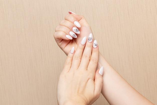 Widok z przodu młoda kobieta pozuje po zabiegu manicure pokazując jej paznokcie piękna pani dziewczyna manicure samoopieka zdrowie moda