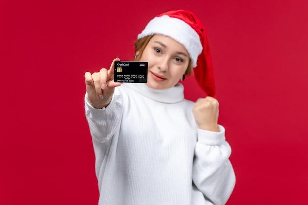 Widok z przodu młoda kobieta pozuje z kartą bankową na czerwonym tle