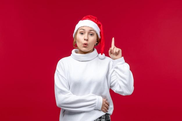 Widok z przodu młoda kobieta próbuje coś powiedzieć na czerwonym tle