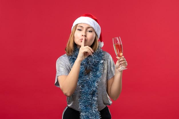 Widok z przodu młoda kobieta prosi o zachowanie ciszy na świątecznej imprezie na czerwonej ścianie