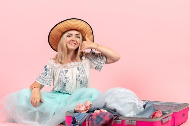 Widok z przodu młoda kobieta przygotowuje się do podróży i demontuje ubrania na różowym tle wycieczka podróż wakacje odpoczynek kolor ubrania