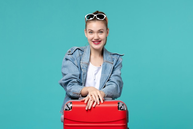 Widok z przodu młoda kobieta przygotowuje się do podróży i śmieje się na niebieskiej przestrzeni