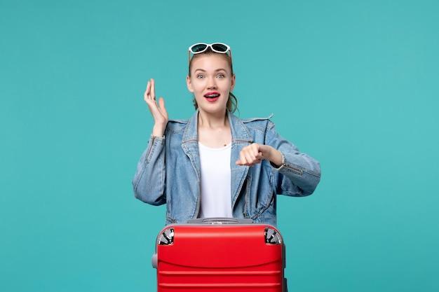 Widok z przodu młoda kobieta przygotowuje się do podróży i sprawdzanie czasu na niebieskiej przestrzeni