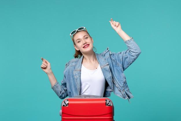Widok z przodu młoda kobieta przygotowuje się do podróży i tańczy na niebieskiej przestrzeni