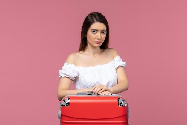 Widok z przodu młoda kobieta przygotowuje się do wakacji i czuje się smutna na różowym tle wycieczka podróż podróż wakacje kobieta za granicą