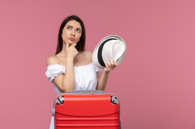 Widok z przodu młoda kobieta przygotowuje się do wakacji i myśli na różowym tle podróż podróż za granicę podróżuje morze