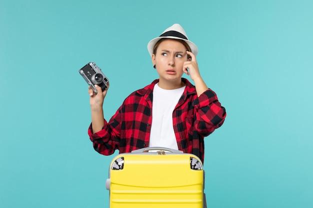 Widok z przodu młoda kobieta przygotowuje się do wakacji i trzyma aparat fotograficzny na niebieskiej przestrzeni