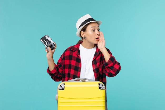 Widok z przodu młoda kobieta przygotowuje się do wakacji i trzyma aparat na niebieskiej przestrzeni