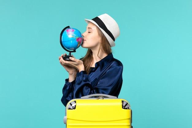 Widok z przodu młoda kobieta przygotowuje się do wakacji i trzyma kulę ziemską całując go na niebieskim tle samolot rejs kobieta morska podróż