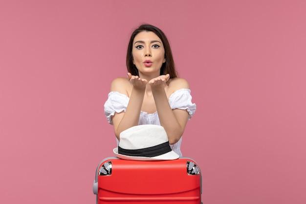Widok z przodu młoda kobieta przygotowuje się do wakacji i wysyła pocałunki na różowym tle podróż podróżująca morską podróż za granicę