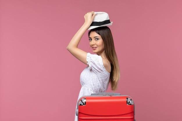 Widok z przodu młoda kobieta przygotowuje się do wakacji na jasnoróżowym tle podróż podróż za granicę podróż morze