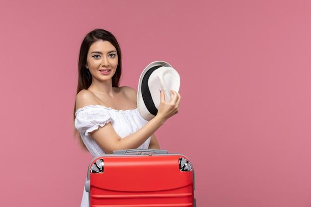 Widok z przodu młoda kobieta przygotowuje się do wakacji na jasnoróżowym tle podróż podróż za granicę podróżująca morze