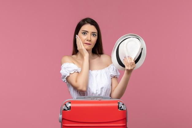 Widok z przodu młoda kobieta przygotowuje się do wakacji na różowym tle podróż podróżująca morską podróż za granicę
