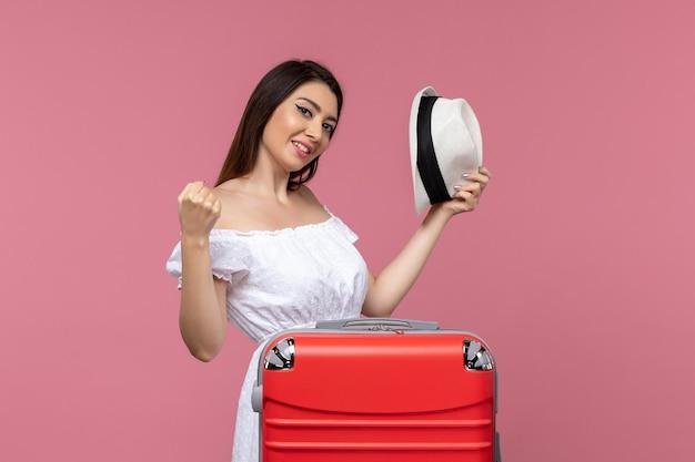Widok z przodu młoda kobieta przygotowuje się do wakacji na różowym tle podróż za granicę podróżując morską podróż