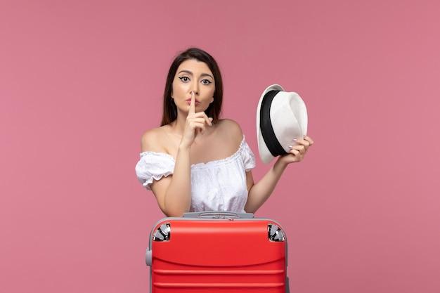 Widok z przodu młoda kobieta przygotowuje się do wakacji na różowym tle podróż zagraniczna podróż morska