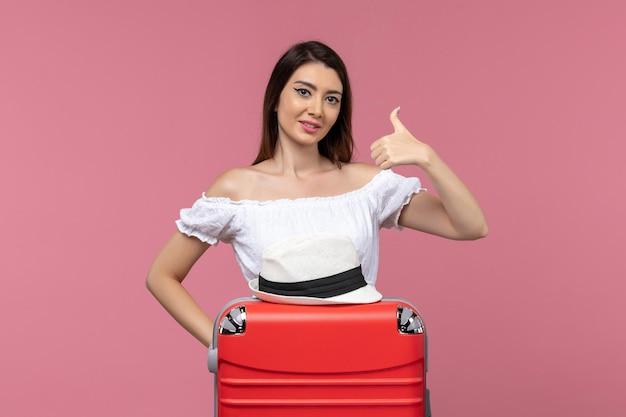 Widok z przodu młoda kobieta przygotowuje się do wakacji na różowym tle podróży podróż zagraniczna podróż morska