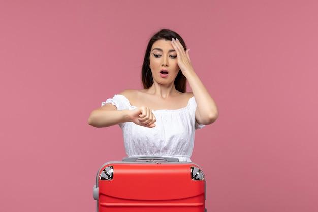 Widok z przodu młoda kobieta przygotowuje się do wakacji sprawdzanie czasu na różowym tle za granicą podróż morska podróż podróż podróż
