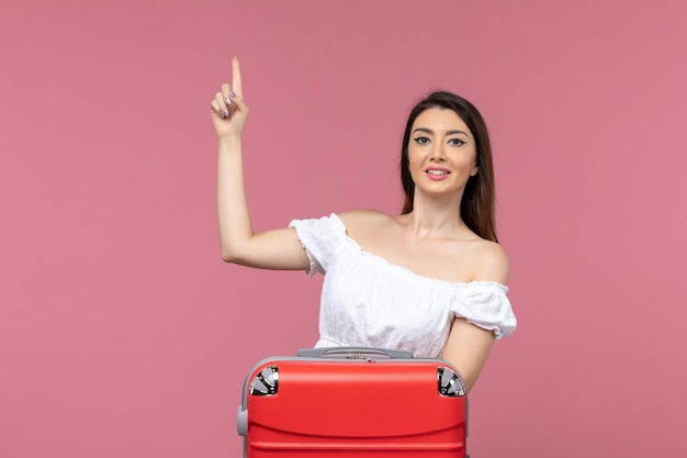 Widok z przodu młoda kobieta przygotowuje się do wakacji z czerwoną torbą na różowym tle podróż za granicę podróż morska podróż