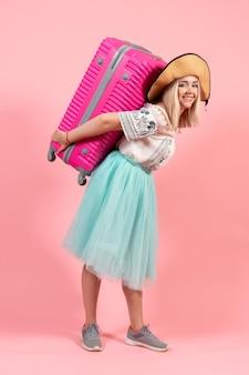 Widok z przodu młoda kobieta przygotowuje się na letnie wakacje niosąc różową torbę na różowym tle wycieczka rejs wakacje morski samolot odpoczynku kolor rest